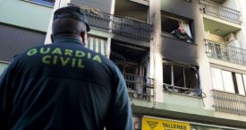 Un agente de la Guardia Civil custodia un edificio incendiado / EFE