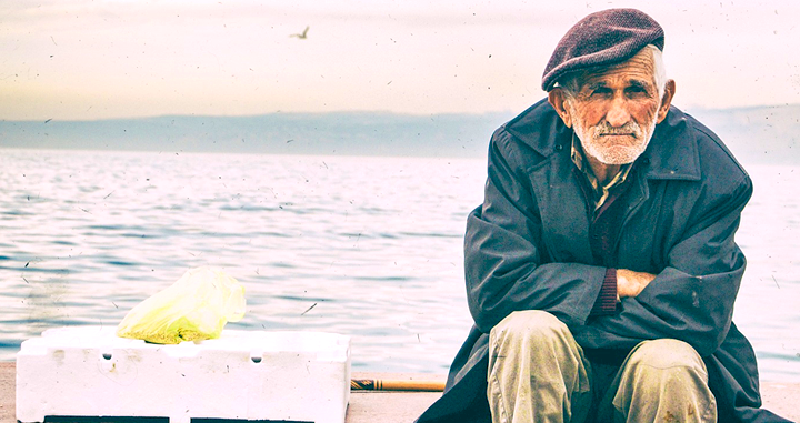 An older man sitting by the seashore / PIXABAY