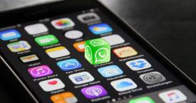 Un iPhone con el logotipo de WhatsApp en tres dimensiones / CG